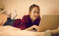 Portrait of teenage girl lying on bed and using laptop cute Stock Photos