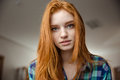 Portrait of thoughtful attractive redhead young woman in plaid shirt