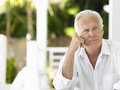 Portrait of thoughtful mature man a sitting on verandah Stock Photo