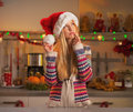 Portrait of thoughtful teenage girl in santa hat in kitchen christmas decorated Stock Photography