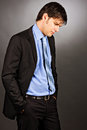 Portrait of a thoughtful young business man looking down on gray background Royalty Free Stock Images