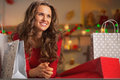 Portrait of thoughtful young woman among christmas shopping bags in decorated kitchen Royalty Free Stock Photos