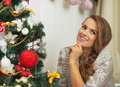 Portrait of thoughtful young woman near christmas tree high resolution photo Royalty Free Stock Image