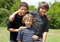 Portrait of three boys smiling adorable two adolescent friends and one little brother diversity the two brothers are mixed race Stock Image