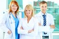 Portrait of three clinicians in white coats looking at camera Stock Images