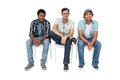 Portrait of three cool young men sitting on chairs over white background Royalty Free Stock Image