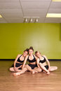 Portrait of three young teenage girls sitting on the wooden floor heads touching and each wearing an identical two piece dance Stock Photography