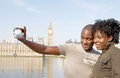 Portrait of tourist couple on westminster close up an african american taking pictures themselves while vacations in london Royalty Free Stock Photos