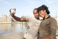Portrait of tourist couple on westminster young african american taking pictures themselves while vacations in london standing in Stock Images