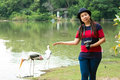Portrait of tourist women standing near pond which two painted storks Royalty Free Stock Photo