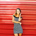 Portrait of trendy stylish girl standing at the red wall backgro Royalty Free Stock Photo