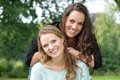 Portrait of two adult sister smiling together outdoors closeup Royalty Free Stock Photography