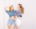 Portrait of two beautiful fashionable girlfriends in denim shorts and striped t-shirt posing nex to the glass wall. Girl holding Royalty Free Stock Photo
