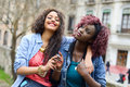 Two beautiful girls in urban backgrund, black and mixed women Royalty Free Stock Photo
