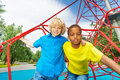 Portrait of two boys stand on red ropes black and caucasian net playground in summer Stock Images