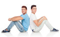 Portrait of two brothers sitting back to back isolated on a white background Royalty Free Stock Photos