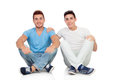 Portrait of two brothers sitting isolated on a white background Stock Photos