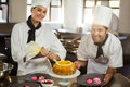 Portrait of two chefs preparing a cake Royalty Free Stock Photo