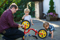 Portrait of two cute boys repairing bicycle wheel with father ou outdoors Stock Images