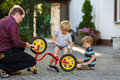 Portrait of two cute boys repairing bicycle wheel with father ou outdoors Royalty Free Stock Image