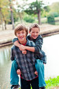 Portrait of two cute young brothers riding piggy back outdoors Royalty Free Stock Photos