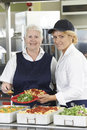 Portrait Of Two Dinner Ladies In School Cafeteria Royalty Free Stock Photo