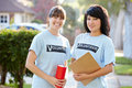 Portrait of two female charity volunteers on street smiling to camera Stock Photography
