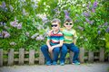 Portrait of two little brothers sitting on small fence in bushes of lilac wearing casual style clothes