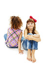 Portrait two little girls sitting back to back smiling white background Royalty Free Stock Photos
