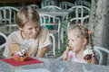 Portrait of two siblings eating Italian gelato ice cream in cafe Royalty Free Stock Photo