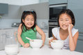 Portrait of two smiling girls sitting with bowls in kitchen young the at home Stock Photo