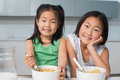 Portrait of two smiling girls sitting with bowls in kitchen young the at home Stock Image