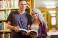Portrait of two students reading book in the library young against a bookshelf Stock Photo