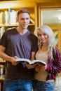 Portrait of two students reading book in the library young against a bookshelf Stock Photography