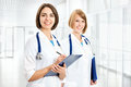 Portrait of two successful female doctors holding a writing pad Stock Image