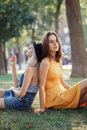 Portrait of two white Caucasian unformal young girls hipster students friends sitting ob grass outside in park Royalty Free Stock Photo