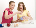 Portrait of two woman friends cooking women on white background Stock Photography