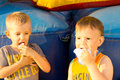 Portrait of two young boys sharing cotton candy a ball sitting near a colorful inflatable bouncer amusement Royalty Free Stock Photos