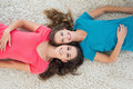 Portrait of two young female friends lying on rug high angle in the living room at home Stock Photos