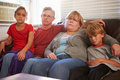 Portrait of unhappy family sitting on sofa together looking at camera Stock Photography