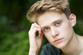Portrait Of Unhappy Teenage Boy Sitting Outdoors Royalty Free Stock Photo