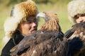 Portrait of unidentified Kazakh hunters holding golden eagles Aquila chrysaetos, circa Almaty, Kazakhstan. Royalty Free Stock Photo