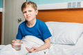 Portrait of unsatisfied boy holding glass of water and medicines in hospital bed Royalty Free Stock Photo