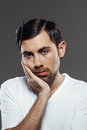 Portrait of upset young man with comb in tangled hair. Royalty Free Stock Photo