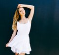 Portrait of very beautiful young blond woman in a short white dress posing on the street near a black wall. Sunny day. The wind bl Royalty Free Stock Photo
