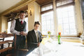 Portrait of waiter and businessman at restaurant table Royalty Free Stock Photo