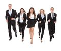 Portrait of welldressed businesspeople running full length against white background Stock Image