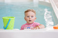 Portrait of white Caucasian baby girl playing with toys in water standing by swimming pool nosing inside, looking in camera, train Royalty Free Stock Photo