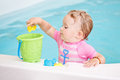 Portrait of white Caucasian baby girl playing with toys in water on swimming pool nosing inside Royalty Free Stock Photo