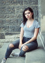 Portrait of white Caucasian beautiful young brunette girl teenager with blue green eyes in ripped jeans, t-shirt, keds Royalty Free Stock Photo